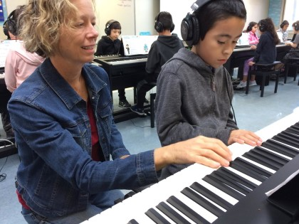 Music instructor Rebecca King works with Dunbar School student Bryan Vasquez Torres